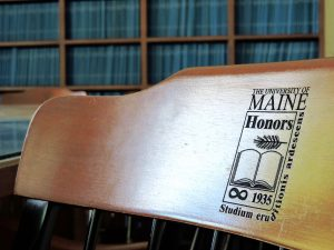 Honors chair in the thesis reading room, with bookshelves of theses shown behind it.