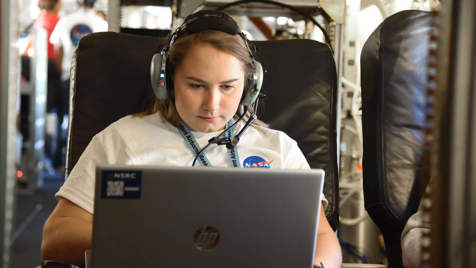 Honors student Laura Paye is shown wearing a headset, using a laptop, wearing a NASA tshirt