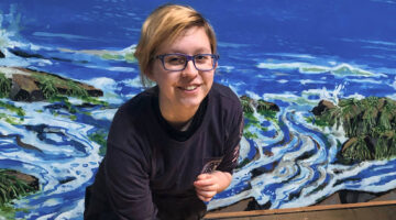 An image of Brynn Yarbrough standing in front of a painting of the ocean.