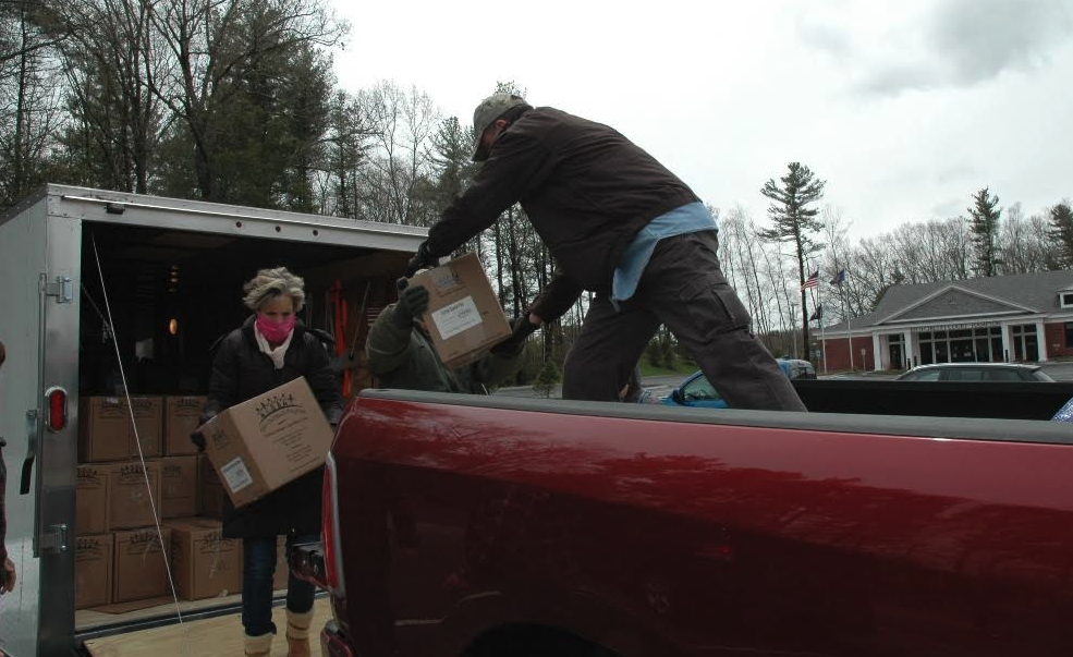 Community members load boxes of food for donation into a truck.