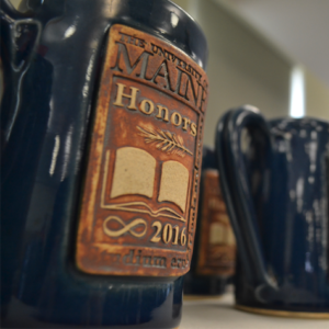 Honors Steins on a table. The stein is blue and has a brown embossed Honors logo on it.
