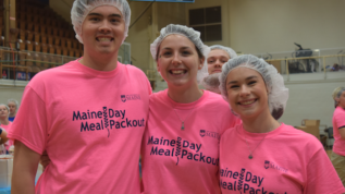 Lauren Ryan (center) volunteers at the 2019 Maine Day Meal Packout along with Alec Penn (left) and Emma Hutchinson (right).