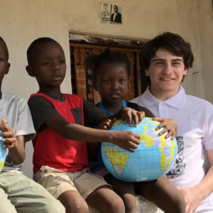 Honors student shown with children in Sierra Leone, June 2019