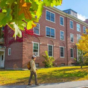 A student walking outside of Colvin Hall, one of the Honors dorms.