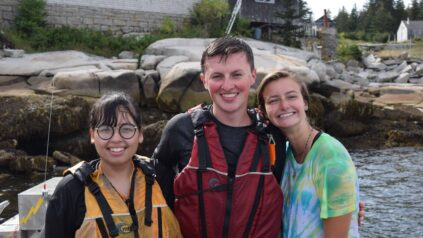 Three Honors students smile together after just having gone on a boating excursion on Hurricane Island.
